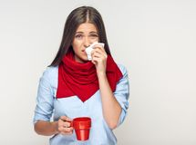 Sick woman blows nose in handkerchief. Red coffee cup. Isolated portrait Royalty Free Stock Photography