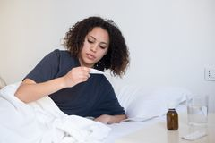 Sick woman checking the result of thermometer Royalty Free Stock Photo