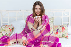 Sick woman covered with blanket holding cup of tea Stock Images