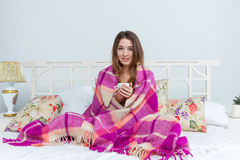 Sick woman covered with blanket holding cup of tea Stock Photo