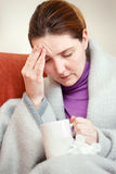 Sick woman covered with blanket at home Stock Image