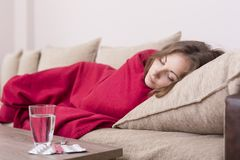 Flu. Sick woman covered with a blanket lying in bed with high fever and a flu. Pills and glass of water on the table Stock Photography