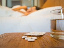 Sick woman covered with a blanket lying in bed with high fever. And a flu, focus on the medicine. Healthcare, medical supplements concept stock images