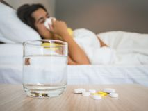 Sick woman covered with a blanket lying in bed with high fever. And a flu, focus on the medicine and glass of water. Healthcare, medical supplements concept Stock Photos