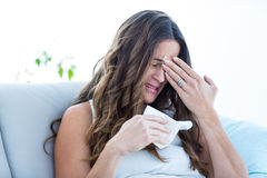 Sick woman crying on sofa Stock Photos