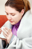 Sick woman with a cup of tea in her hand Stock Photos