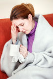 Sick woman with a cup of tea in her hand Royalty Free Stock Photography