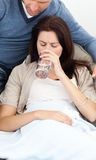 Sick woman drinking water lying on the sofa Stock Image