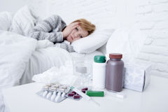 Sick woman feeling bad ill lying on bed suffering headache winter cold and flu virus having medicines Royalty Free Stock Photos