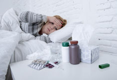 Sick woman feeling bad ill lying on bed suffering headache winter cold and flu virus having medicines. Young sick woman feeling ill and bad lying on bed Stock Photography