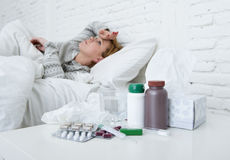 Sick woman feeling bad ill lying on bed suffering headache winter cold and flu virus having medicines Stock Images