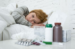 Sick woman feeling bad ill lying on bed suffering headache winter cold and flu virus having medicines Royalty Free Stock Image