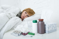 Sick woman feeling bad ill lying on bed suffering headache winter cold and flu virus having medicines Royalty Free Stock Images