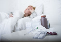 Sick woman feeling bad ill lying on bed suffering headache winter cold and flu virus having medicines. Young sick woman feeling ill and bad lying on bed Royalty Free Stock Images