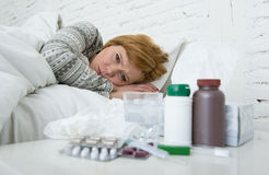 Sick woman feeling bad ill lying on bed suffering headache winter cold and flu virus having medicines Stock Image