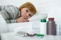 Sick woman feeling bad ill lying on bed suffering headache winter cold and flu virus having medicines Royalty Free Stock Photo