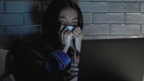Sick woman with fever sneezing tissue in bed at night, working on laptop. Stock footage stock footage