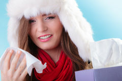 Sick woman with fever sneezing in tissue. Winter time. Stock Photos