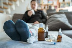 Sick woman with flu, cold, fever or virus sitting on sofa at home royalty free stock photos