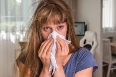 Sick woman with flu or cold sneezing into handkerchief Stock Image