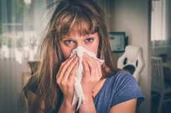 Sick woman with flu or cold sneezing into handkerchief. At home - retro style Stock Image