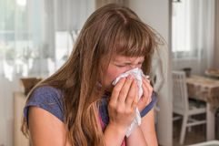 Sick woman with flu or cold sneezing into handkerchief Royalty Free Stock Photos