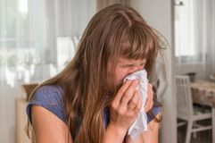 Sick woman with flu or cold sneezing into handkerchief Royalty Free Stock Photo