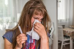 Sick woman with flu or cold sneezing into handkerchief Stock Photo