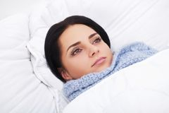 Sick Woman. Flu. Girl with cold lying under a blanket holding a Royalty Free Stock Photography