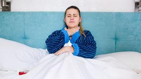 Portrait of sick woman with flu lying in bed and holding hand on aching throat royalty free stock photos
