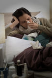 Sick woman with flu sneezing in bed Stock Photo