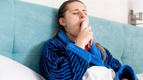 Portrtaif of sick woman with flu using sore throat spray. Sick woman with flu using sore throat spray stock photo