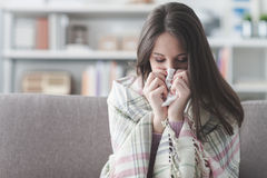 Sick woman with flu. Sick young woman at home on the sofa with a cold, she is covering with a blanket and blowing her nose royalty free stock photography