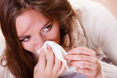 Sick woman girl with fever sneezing in tissue Stock Photos
