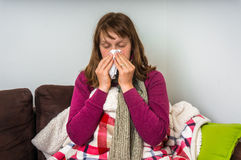 Sick woman having flu and blowing her runny nose Stock Images