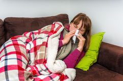 Sick woman having flu and blowing her runny nose Stock Photography