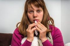 Sick woman having flu and sneezing into handkerchief Stock Photos