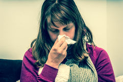 Sick woman having flu and sneezing into handkerchief Stock Images