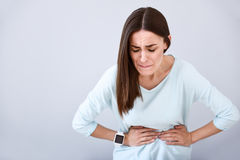Sick woman having a stomach ache. In dire need if recovery. Beautiful sick woman holding her hands on the stoma and feeling terrible ache while standing isolated Stock Photo