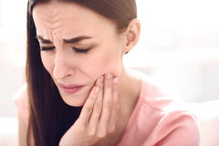Sick woman having a toothache. Do not wait for consequences. Portrait of beautiful sick woman holding touching her jaw and feeling pain while having a toothache Royalty Free Stock Photos