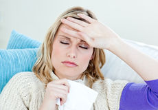 Sick woman with headache lying on the sofa at home Royalty Free Stock Image