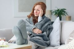 Sick woman with headache. Sick woman with a headache sitting on a sofa at home wrapped in grey blanket Royalty Free Stock Photo