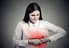 Sick woman with heart attack, pain, touching her chest colored in red with hands royalty free stock photo