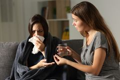 Sick woman and her friend giving painkiller pill Royalty Free Stock Image