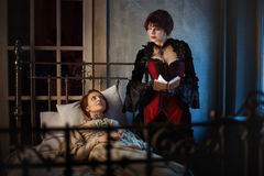 Sick woman and her friend. Sick women lying on a bed next to another women reading a book, in the Gothic style retro Stock Images