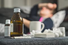 Sick woman holding head and forehead with hand and arm. Medicine, thermometer, hot beverage and dirty paper towels in front. Person having flu, fever and Royalty Free Stock Images