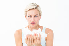 Sick woman holding tissues looking at camera Royalty Free Stock Images
