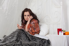 Sick woman lies in a house bed. Stock Photo