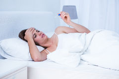 Sick woman looking at her thermometer Stock Image