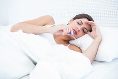 Sick woman looking at her thermometer Stock Photo
